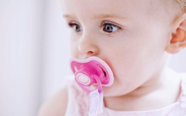 Baby with orange pacifier in his mouth with white background