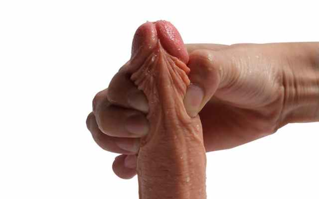 close-up of squishy realistic dildo being squeezed at the shaft by a hand