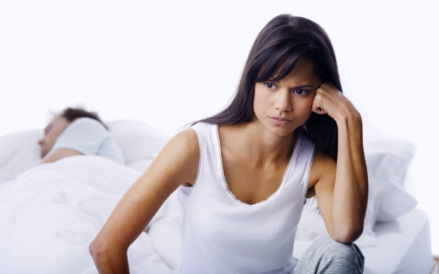 frustrated woman sitting at edge of bed while her boyfriend sleeps