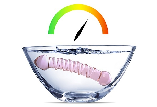 Glass dildo in a bowl of water with temperature gauge graphic above it