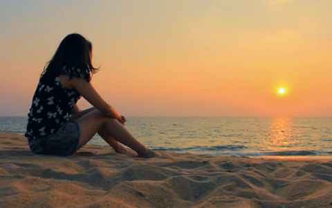 young woman sitting on the beach while the sun sets