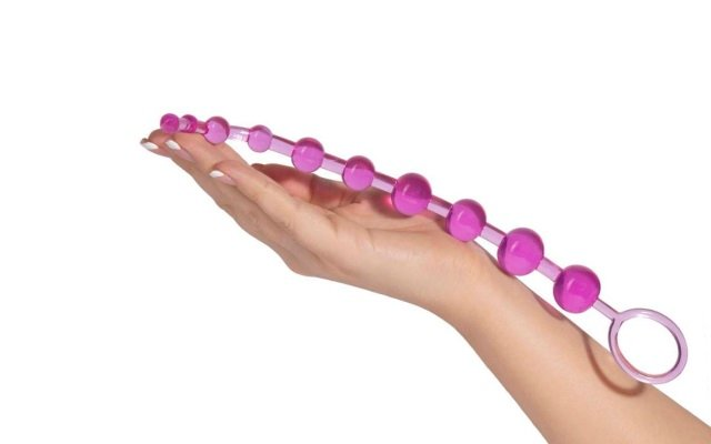 Luxurious pink anal beads resting in mwoman's hand