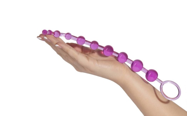 Luxurious pink anal beads resting in hand of mwoman
