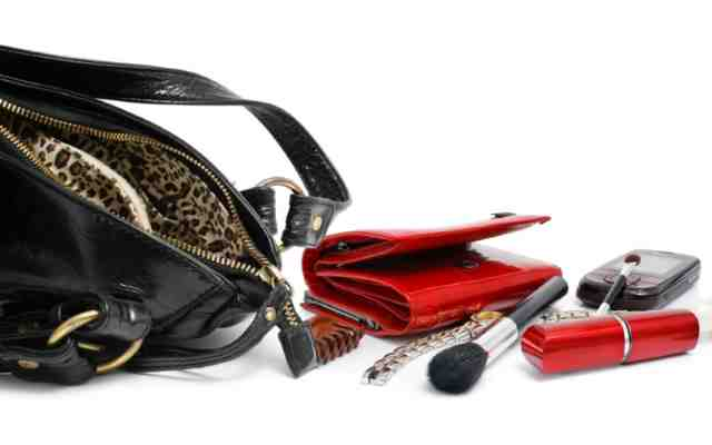 Empty black leather purse revealing wallet and other beauty accessories