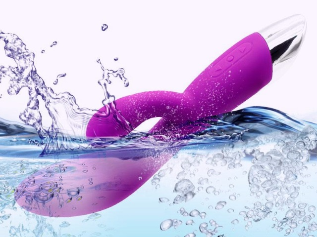 A purple vibrator being immersed in water