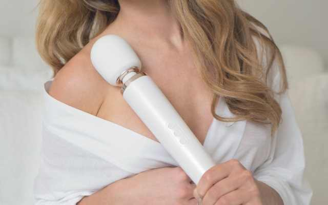 Blonde woman in white top holding up a white wand vibrator